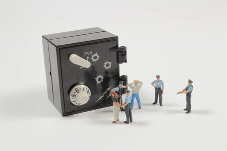 figure toys of police catch the thief before they open the safety box. concept of criminal. Stock Photo