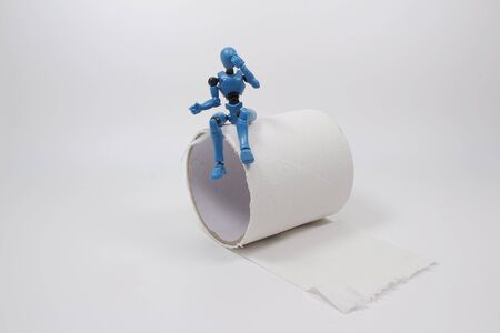 the scale of mannequin sit on a roll of toilet paper. Reklamní fotografie