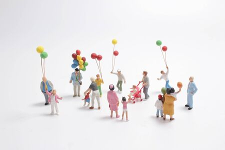 mini people with family holding balloon on the board