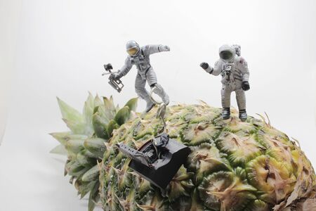 Astronaut in an white suit fly around the pineapple