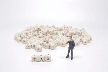 The word tax on wooden cube block with figure