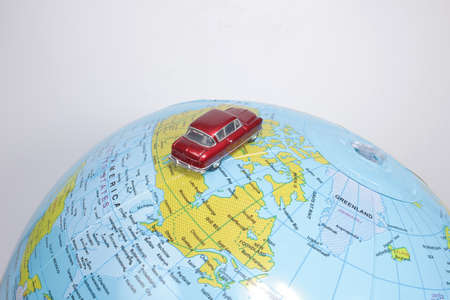 figure toy car on geographical globe of earth
