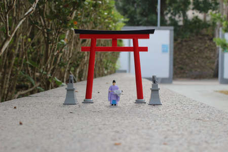 the scale of figure Kannushi men with Torii gate Stock Photo