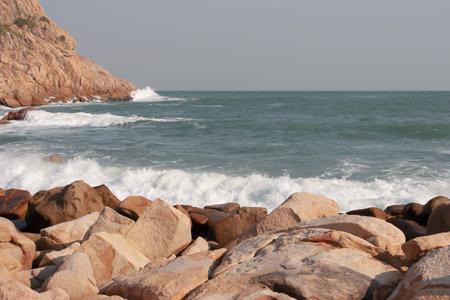 a rocky sea coast and blurred water in shek o