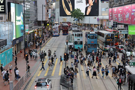 busy commuters crossing street in downtown district, causeway bay, hong kong