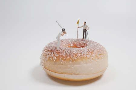 the mini figure play the golf on on Doughnut 版權商用圖片