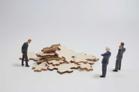 a mini businessmen standing investment in Solve puzzles 版權商用圖片