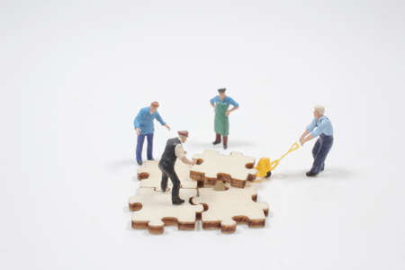 Teamwork puzzle concept, figure assembling jigsaw puzzle 版權商用圖片