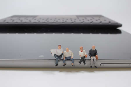 mini figure sitting on a laptop while working on a laptop and another businessman 版權商用圖片