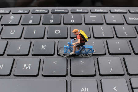 the model of man riding his bike on the laptop PC keyboard