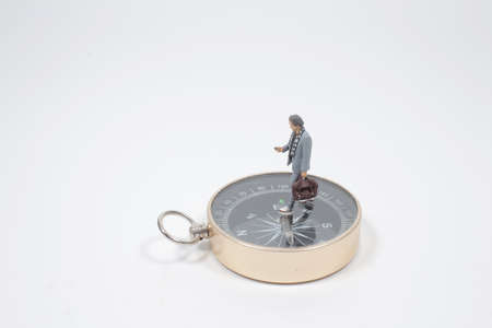 mini figure business man standing on compass in the center