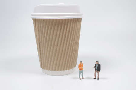 a mini figure are enjoy the coffee with the paper mug