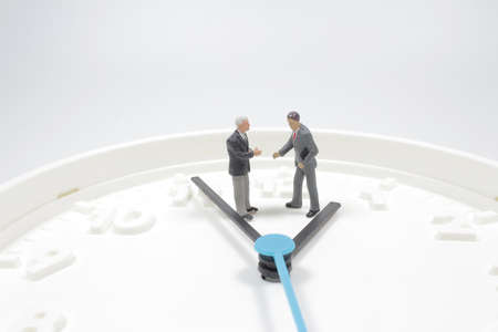 business or time concept as miniature businessman standing on clock 版權商用圖片