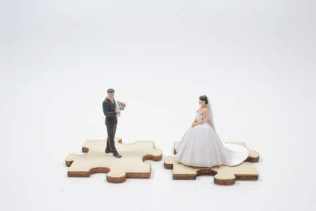 the mini Bride and groom married miniature people standing on jigsaw