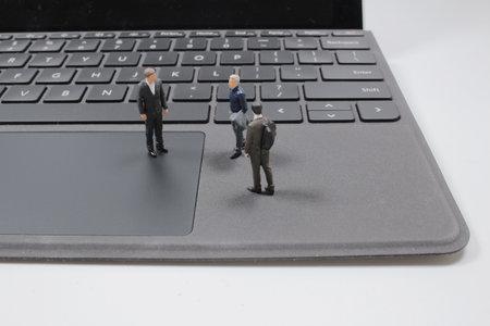 the mini of fun Businessmen on a laptop