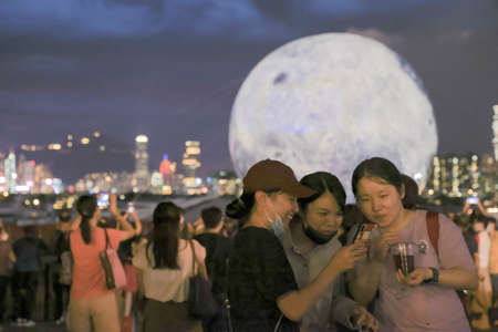 21 Sept 2021 People pose for pictures against the backdrop of a huge glowing moon floating in the Kwun Tong typhoon shelter