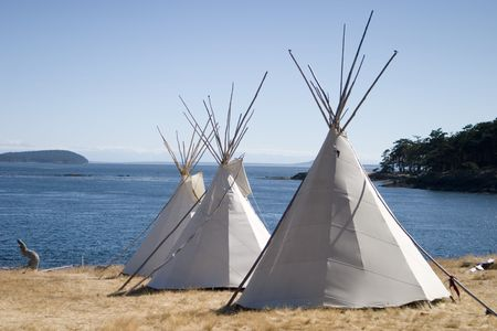 Three teepees near water