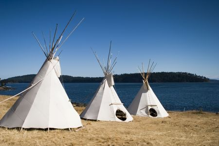 Three teepees together are lined up in a row Imagens