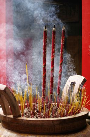 An urn in a Buddhist temple with incense and larger prayer sticks photo