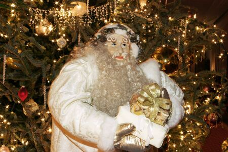 saint nick: Saint Nick at night with a full beard and in a white robe bearing a gift. He is in front of a Christmas tree lit up with lights, gold balls, and other decorations.