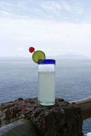 resulted: A tall glass of lemonade with a slice of green lime and a bright red cherry in front of an ocean view in Puerto Vallarta. The cool drink in the tropical climate has resulted in drops of condensation on the outside of the glass. Stock Photo