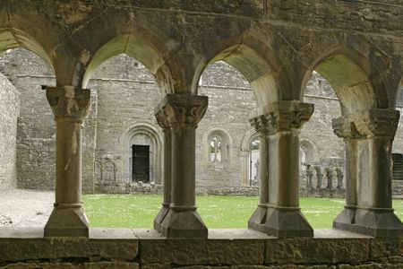 The inner courtyard of an ancient abbey in the village of Cong in the Irish countryside. This view, from under a covered walkway, shows the old pillars and the inside walls.