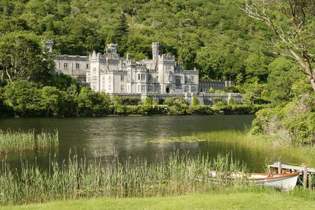 abbey: An Irish castle in the countryside. Located next to a lake, this was originally the residence for Irish nobility and is now a convent and girls school. The white skiff in the foreground is common. Stock Photo