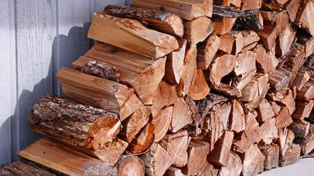 A pile of split firewood neatly stacked and organized in front of a shed. Stock Photo