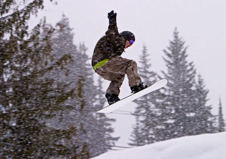 A man on a snowboard performing a jump. The arms are windmilling to stay in balance. It was snowing heavily and the snowflakes are motion-blurred as I panned with the boarder.
