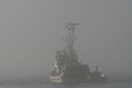 A fishing boat disappearing into deep fog while looking for fish in the Puget Sound. photo