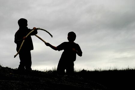 dueling: Two boys are dueling with sticks near a beach in Washington State. They are outlined by the cloudy sky in the background.