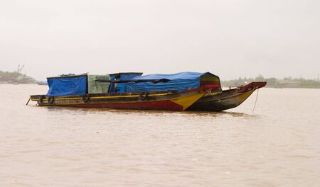 laden: Two river boats at anchor in the Mekong River delta in Vietnam that are fully loaded with cargo and covered with blue tarps.