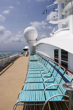 A line of aqua-blue deck chairs are organized along a walkway on a cruise ship.