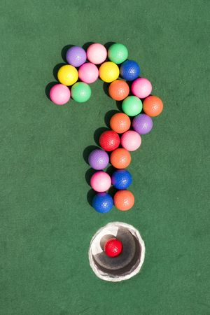 gaily: A number of gaily colored golf balls formed into the shape of a question mark, using the silver cup as the period marker. Stock Photo