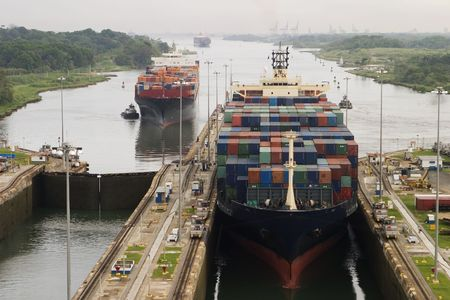 Several freighters, assisted by tugboats, are entering the Panama Canal at Gatun Locks on the Atlantic side. These container ships are fully loaded with cargo heading west towards the Pacific. Stock Photo