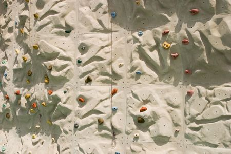 belaying: A detailed view of an artificial climbing wall with multi-colored holds spread throughout the wall. A close look shows two cables used for belaying.
