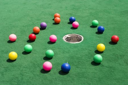 A number of brightly colored golf balls scattered around the hole on a practice putting green. Stock Photo