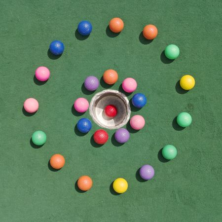 Two concentric circles of golf balls surrounding a hole with a red golf ball thats made a hole-in-one.