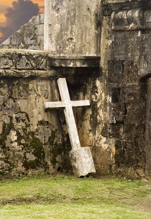 crumbling: An almost white crucifix, pulled from the ground, is leaning against the walls of an old abandoned building that is slowly crumbling. The image portrays a sense of melancholy loneliness.