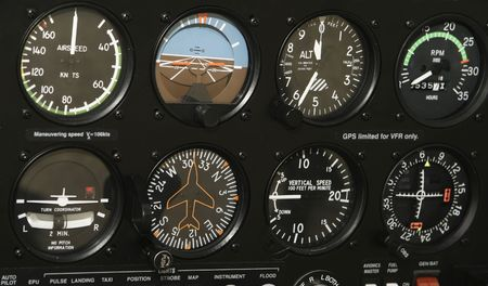 A control panel in a small airplane is filled with indicators and various controls.
