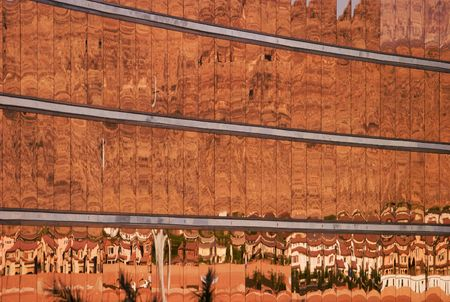 distort: Gold-tinted windows on the facade of a hotel reflect a housing development and the red rocks of a mountain range in the background with a series of Dali-esque distortions. Stock Photo