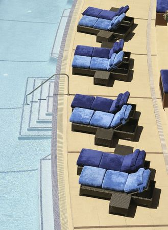 A set of eight blue lounging chairs by the side of a aqua blue swimming pool at a Nevada resort. Stock Photo - 1052545