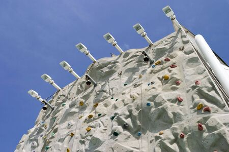A view of the top of a climbing wall from below.