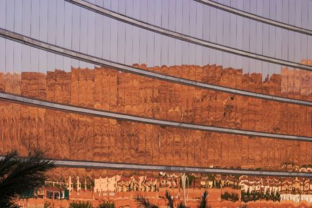 distort: Gold-tinted windows on the facade of a hotel reflect the peaks of a nearby mountain range looming over a housing development with a series of Dali-esque reflections.
