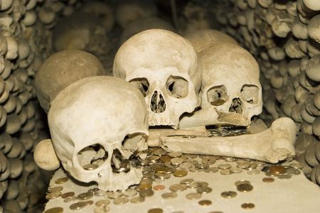 grisly: Bones and coin offerings are shown in a detailed view of one of the crypts at the ossuary in Kutna Hora. Stock Photo