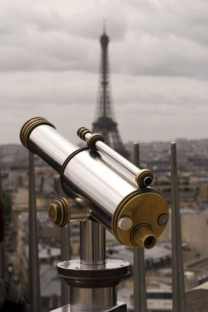 A bright and shiny telescope on the Arc de Triomphe in Paris with the Eiffel Tower in the background. Imagens