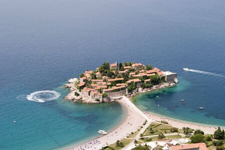 Aerial view of Sveti Stefan showing the resort on its peninsula with the causeway connecting to the surrounding beaches and the blue water of the Adriatic Sea.
