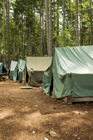 Tents at summer camp. A group of five tents form a campsite in a clearing in the forest. Stock Photo