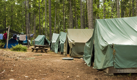 campsite: Boy Scout Campground. A typical campsite at a Boy Scout Camp includes tents, a table, dirt, and dirty clothes drying on a rope.
