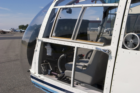 A view inside the plexiglass windows of a helicopter cockpit.